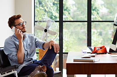 Buy stock photo Shot of a young man talking on a cellphone while sitting in his home office