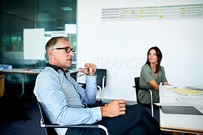 Buy stock photo Shot of colleagues having a meeting around a boardroom table in an office