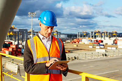 Buy stock photo Shot of a man in workwear standing on a walkway using a digital tablet over at a large commercial dock
