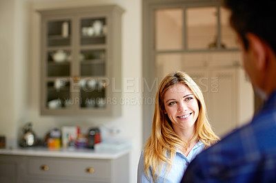 Buy stock photo Shot of a young couple drinking talking together in their kitchen