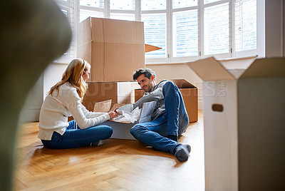 Buy stock photo Shot of a happy young couple unpacking boxes in their new house