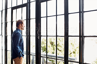 Buy stock photo Shot of a mature man deep in thought while looking through a window at home