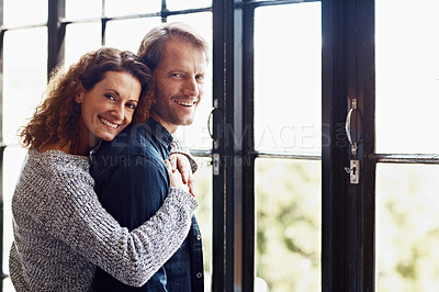 Buy stock photo Portrait of an affectionate mature couple hugging in front of a window at home