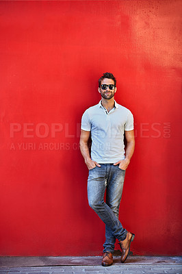 Buy stock photo Portrait of a stylish young man leaning against a red wall outside