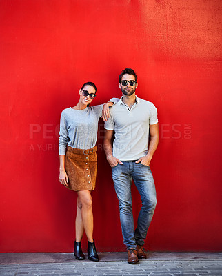Buy stock photo Portrait of a stylish young couple leaning against a red wall outside