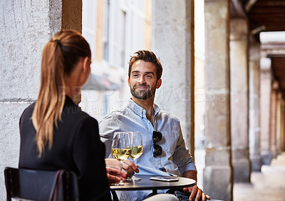 Buy stock photo Shot of a young couple sitting at a sidewalk table drinking wine and talking together