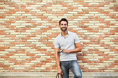 Buy stock photo Portrait of a stylish young man leaning against a brick wall outside
