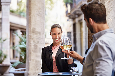 Buy stock photo Shot of a young couple sitting at a sidewalk table toasting with wine together
