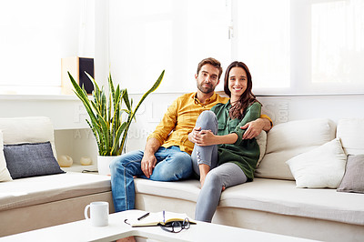 Buy stock photo Portrait of a smiling young couple relaxing on their sofa at home