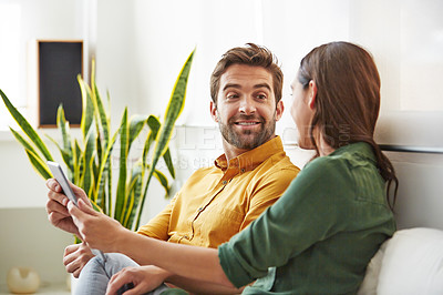 Buy stock photo Shot of a smiling young couple using a digital tablet together while relaxing in their living room