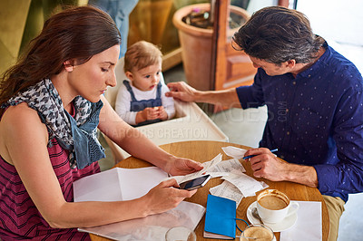 Buy stock photo Shot of a woman going through bills at a cafe with her husband and baby girl next to her