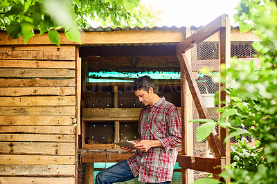 Buy stock photo Shot of a mature man using a digital tablet while standing in his organic garden