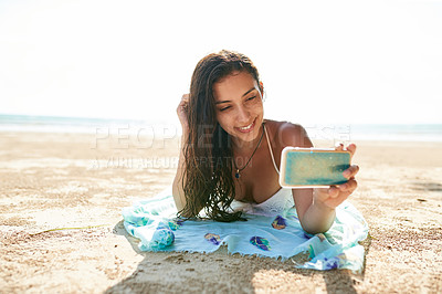 Buy stock photo Shot of a young woman taking a selfie while lying on the beach