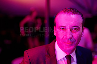 Buy stock photo Shot of a seedy businessman in a neon lit go go bar with a woman dancing on a pole behind him