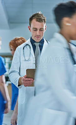 Buy stock photo Shot of a young doctor reading the contents of a patient's file in a busy hospital