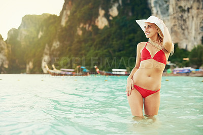 Buy stock photo Shot of a young woman posing with her bikini in the water