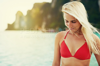 Buy stock photo Shot of a young woman spending the day at the beach