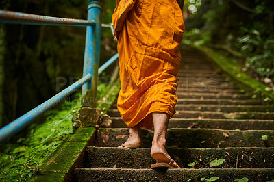 Buy stock photo Rearview shot of a buddhist monk climbing a flight of stone steps
