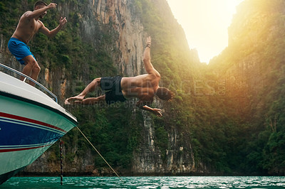 Buy stock photo Shot of a young man doing a backflip off a boat while his friends watch