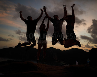 Buy stock photo Shot of a group of jumping friends silhouetted against a sunset