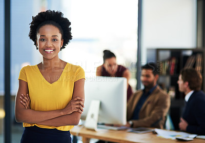 Buy stock photo Portrait of a young businesswoman standing in an office with her colleagues in the background