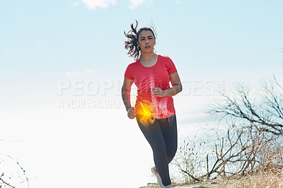 Buy stock photo Shot of an attractive young woman running outdoors with her hip injury highlighted