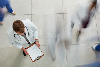 Buy stock photo High angle shot of a male doctor looking at a patient's file in a busy hospital