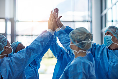 Buy stock photo Cropped shot of a team of medical practitioners high fiving together in a hospital
