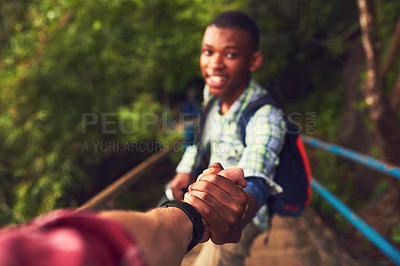 Buy stock photo POV shot of a young man helping a friend up a mountain trail