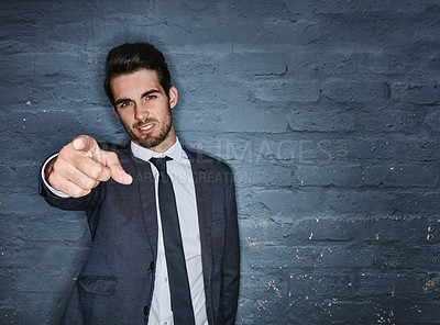 Buy stock photo Shot of a handsome businessman pointing towards you against a grey brick wall