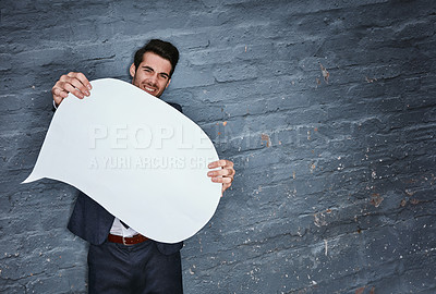 Buy stock photo Shot of a businessman holding a speech bubble against a grey wall