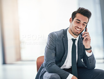 Buy stock photo Shot of a trendy young businessman talking on his cellphone in the office