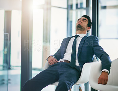 Buy stock photo Shot of an exhausted young businessman resting on a chair in the office