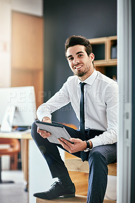 Buy stock photo Portrait of a trendy young businessman using his tablet while sitting on the stairs in his office
