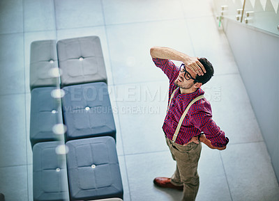Buy stock photo High angle shot of a frustrated young designer standing in his office