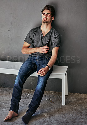 Buy stock photo Full length shot of a beaten and bruised young man sitting on a bench