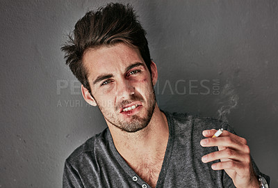 Buy stock photo Cropped portrait of a beaten and bruised young man smoking a cigarette