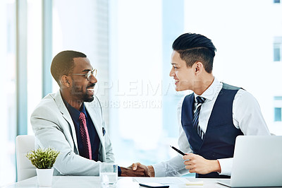 Buy stock photo Cropped shot of colleagues shaking hands while sitting in the office