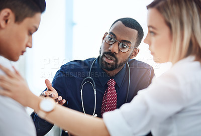 Buy stock photo Cropped shot of a young couple having a consultation with their doctor