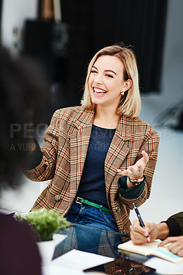 Buy stock photo Shot of a young woman having a discussion with her colleagues during a meeting