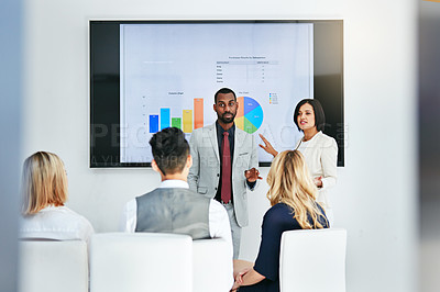 Buy stock photo Shot of a businessman and businesswoman giving a presentation to their colleagues at work