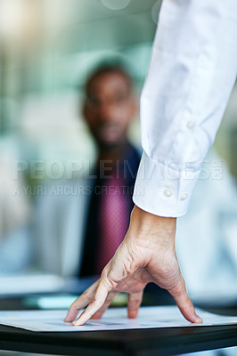 Buy stock photo Cropped shot of a hand on top of a document during a meeting at work