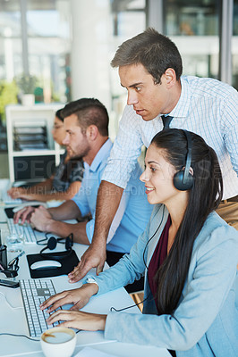 Buy stock photo Shot of a young man assisting his colleague in a call center
