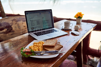 Buy stock photo Shot of a laptop and freshly made breakfast on a table outside