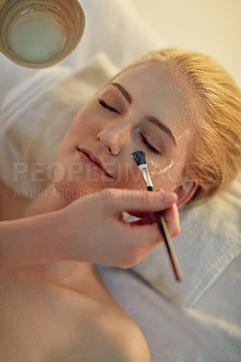 Buy stock photo Cropped shot of a young woman getting a facial treatment at a spa