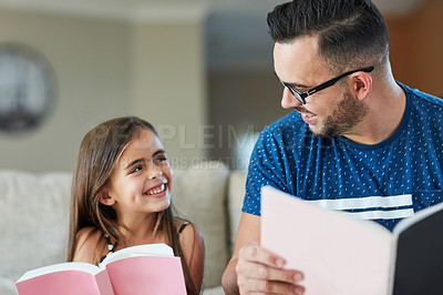 Buy stock photo Cropped shot of a father an daughter reading together at home