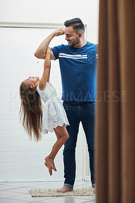 Buy stock photo Shot of a little girl holding on to her father's arm as he lifts her up