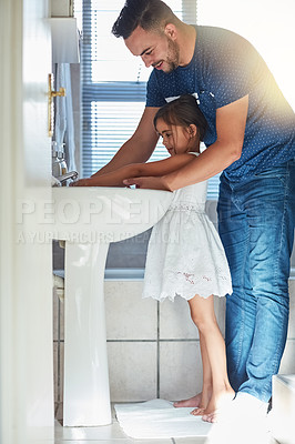 Buy stock photo Shot of a father helping his little daughter wash her hands at the bathroom sink
