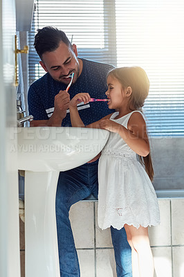 Buy stock photo Cropped shot of a father and daughter brushing their teeth together at the bathroom sink