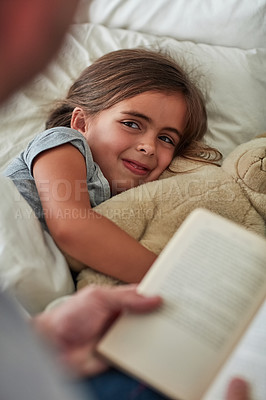 Buy stock photo Cropped shot of a little girl lying in bed while her father reads her a story